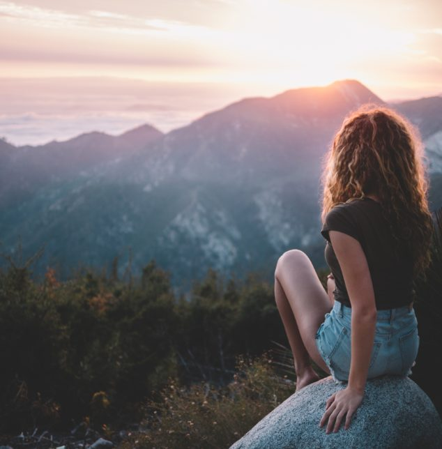 A woman on a rock watching a sunset in the mountains, when looking for a good teen therapist in Frankfort.