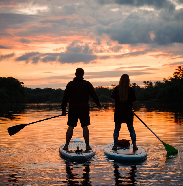 An image of a couple standing on paddle boards with oars in their hands on the river at sunset who've met with a Frankfort marriage counselor.
