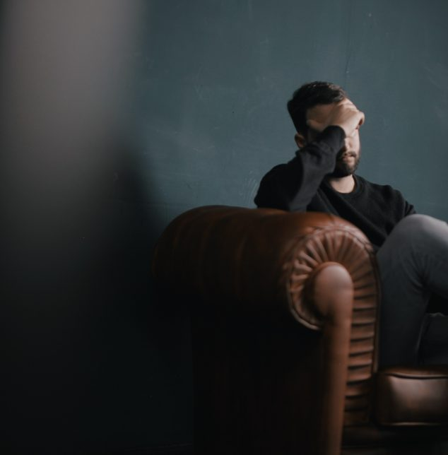 An unhappy man sitting in a chair covering his face before contacting Counseling works for Frankfort anxiety counseling.