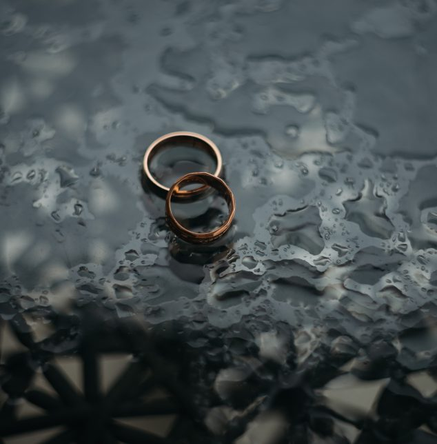 Two wedding rings in a puddle of water representing how you can benefit from Plainfield trauma counseling.