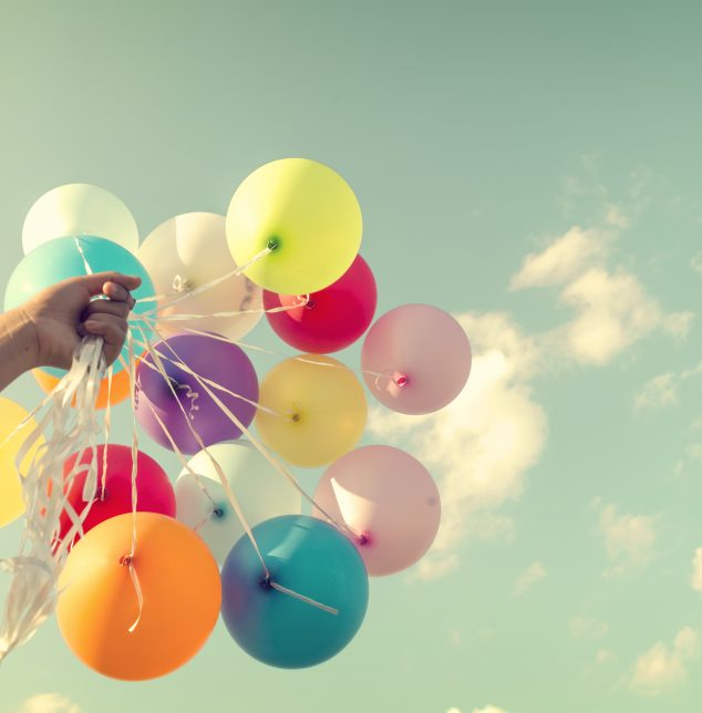 A girl holding colorful balloons in her hand representing how our Naperville therapists will help you understand all your emotions